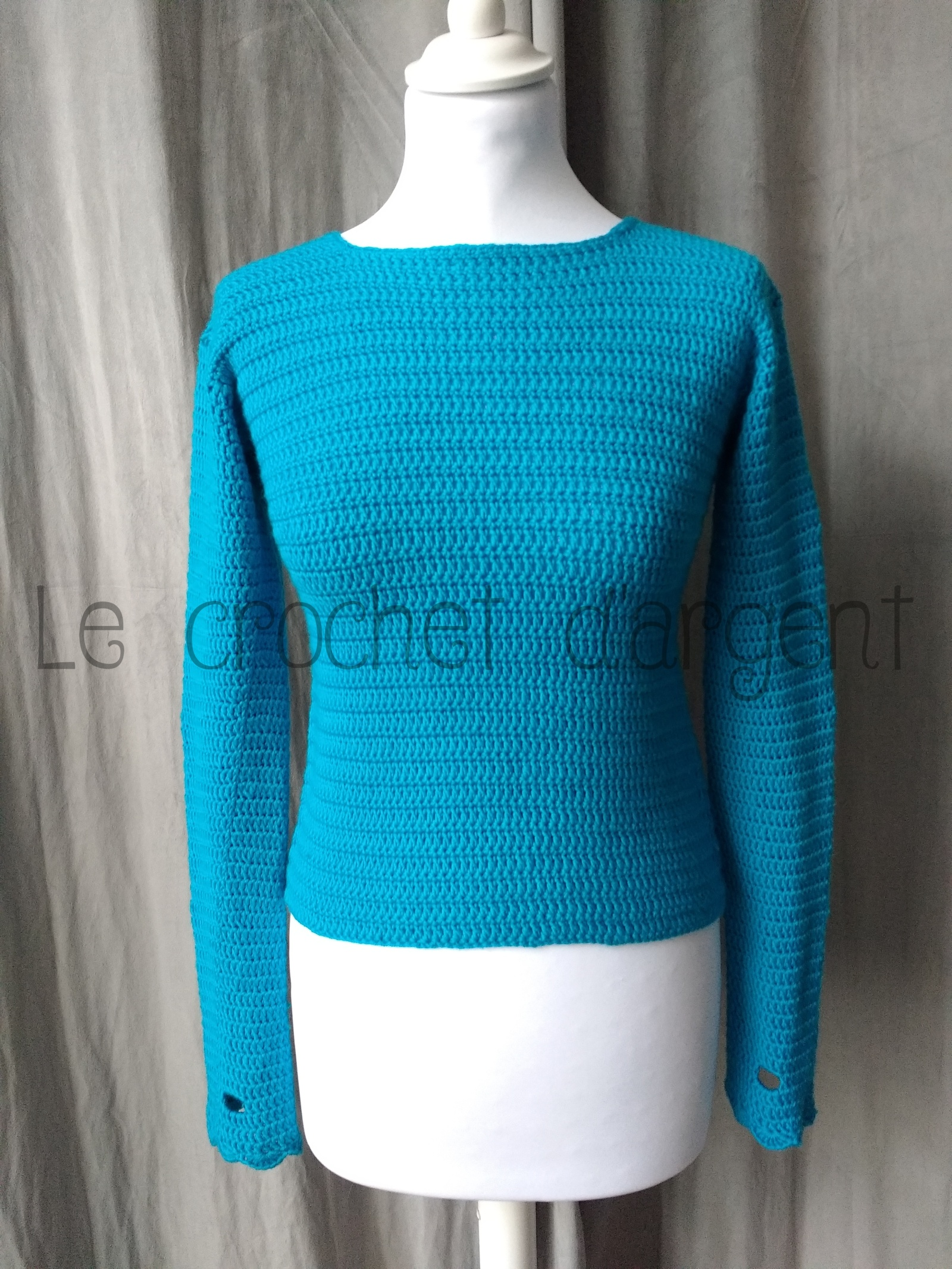 A turquoise blue crocheted sweater with mittens and free pattern